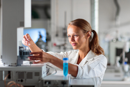 laboratory research: Portrait of a female researcher doing research in a chemistry lab (shallow DOF; color toned image)