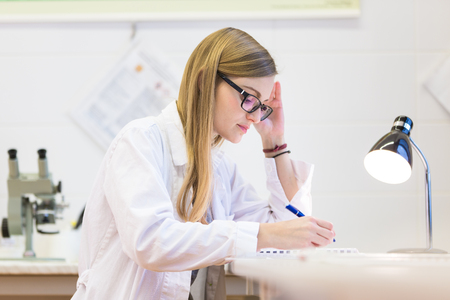 health professional: Portrait of a female researcher doing research in a chemistry lab (shallow DOF; color toned image)
