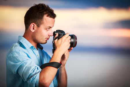 Handsome young photographer using his modern DSLR outdoors, against lovely sky backdrop (color toned image;shallow DOF)