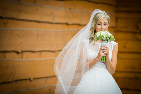Gorgeous bride on her wedding day  holding her lovely bouquet (color toned image; shallow DOF) Stock Photo