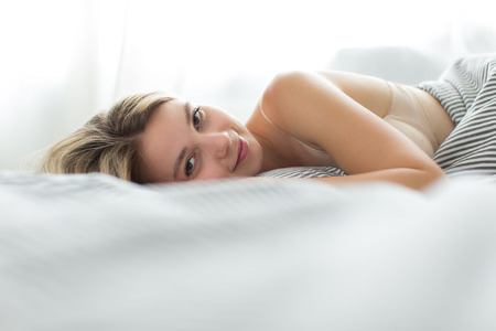 woman young: Beautiful young woman sleeping in bed (color toned image; shallow DOF)