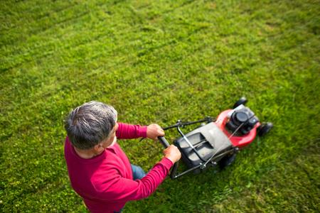 Älterer Mann, seinen Garten zu mähen - Schuss von oben - interessante Winkelansicht