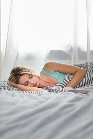 wellness sleepy: Beautiful young woman sleeping in bed (color toned image; shallow DOF)