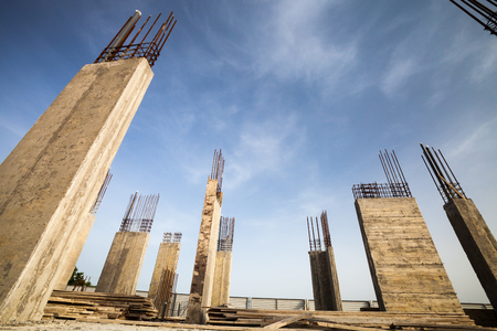 Construction site - Pillars of a building in the making against blue sky Stock Photo