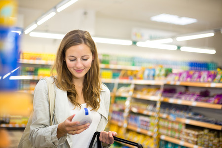 Beautiful young woman shopping in a grocery storesupermarket (color toned image)