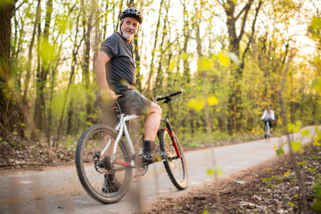 handsome old man: Senior man on his mountain bike outdoors (shallow DOF; color toned image)