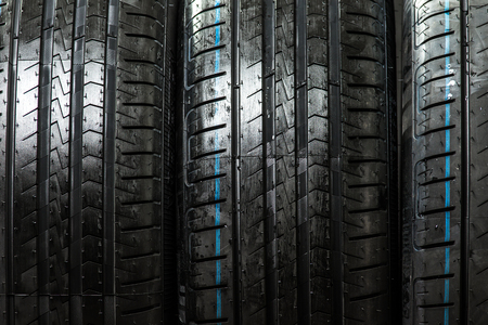 lowkey: Stack of brand new high performance car tires on clean low-key black studio background