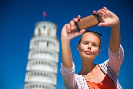 Gorgeous young woman taking a selfie with her smart phone in front of the Leaning Tower of Pisa, Tuscany, Italy (shallow DOF)