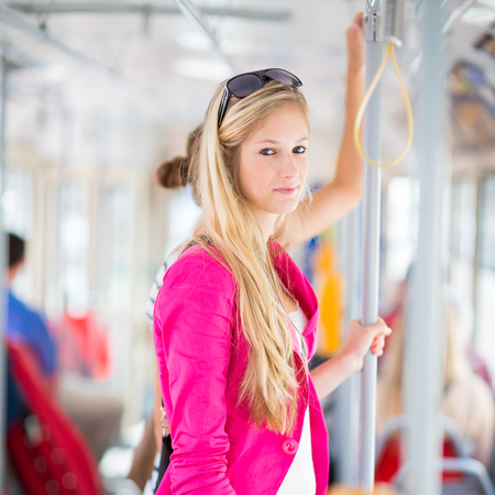 tramway: Pretty, young woman on a streetcartramway, during her commute to work (color toned image; shallow DOF)