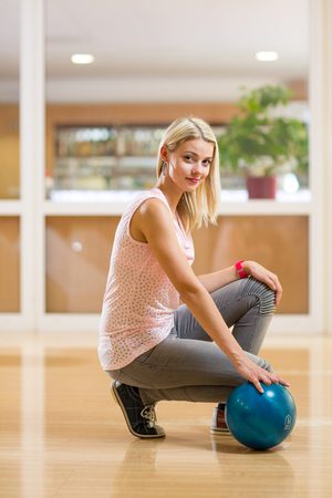 Pretty, young woman holding a bowling ball at the bowling club, ready to bowl (color toned image; shallow DOF) Stock Photo