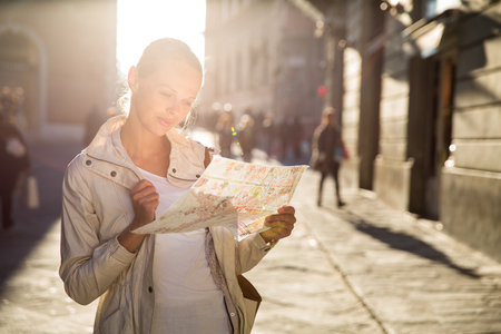 discovering: Gorgeous female tourist with a map discovering a foreign city (shallow DOF; color toned image)