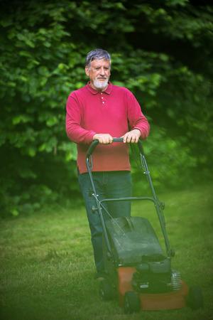 Senior Mann den Rasen in seinem Garten zu mähen