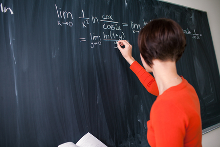 Pretty, young college student writing on the chalkboard/blackboard during a math class (color toned image) photo