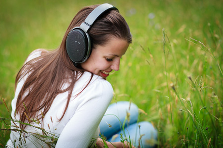 portrait of a pretty young woman listening to music on her mp3 player outdoors (daydreaming) photo
