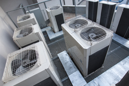 Air conditioning equipment atop a modern building - aerialdrone view of the roof with all the necessary installations Stock Photo