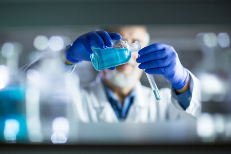 scientific research: Senior male researcher carrying out scientific research in a lab (shallow DOF; color toned image)