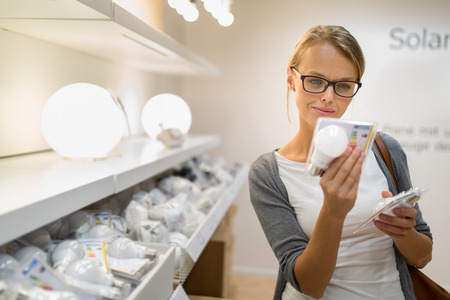 Energy efficient lighting choice: Pretty, young woman holding and choosing a LED diode light bulb for her lamp in DIY department store