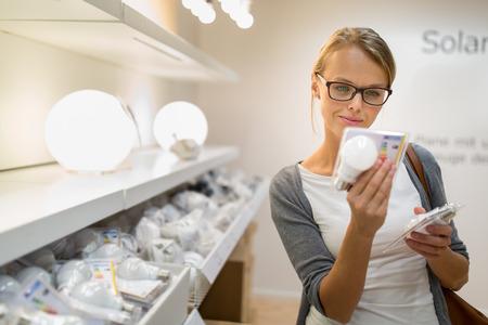 Energie-efficiënte verlichting keuze: Mooie, jonge vrouw bedrijf en het kiezen van een LED-diode gloeilamp voor haar lamp in doe-het-warenhuis
