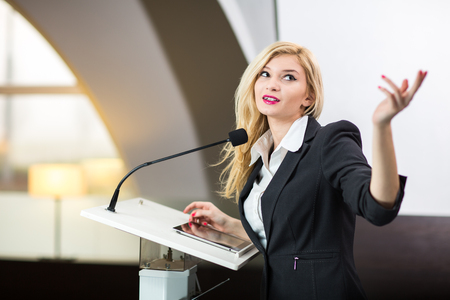 Bastante, joven mujer de negocios dando una presentación en un entorno de conferencia / reunión (DOF, imagen en color entonado) Foto de archivo - 67027576