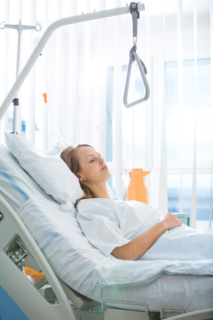 Pretty, young, female patient in a modern hospital room. Getting better fast after a surgery - pensive yet positive, thinking ahead, making plans (shallow DOF; color toned image)