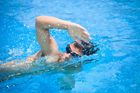 Young man swimming the front crawl in a pool photo