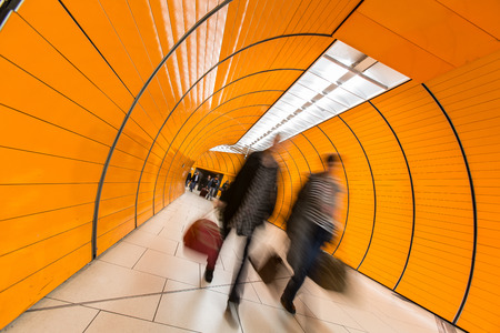convey: People rushing through a subway corridor (motion blur technique is used to convey movement)