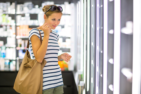 Young woman shopping for the right fragrance/perfume photo