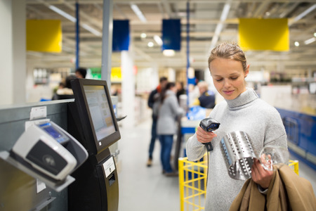 Mooie, jonge vrouw met behulp van self-service kassa in een winkel (ondiepe DOF, kleur getinte afbeelding)