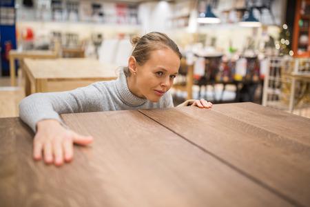 Mooie, jonge vrouw het kiezen van de juiste meubels voor haar appartement in een moderne winkel voor woninginrichting (kleur getinte afbeelding, ondiepe DOF)
