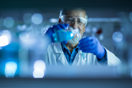 chromatograph: Senior male researcher carrying out scientific research in a lab (shallow DOF; color toned image)