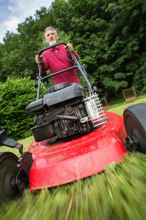 Senior Mann den Rasen in seinem Garten zu mähen (selektive Fokus, flache DOF)