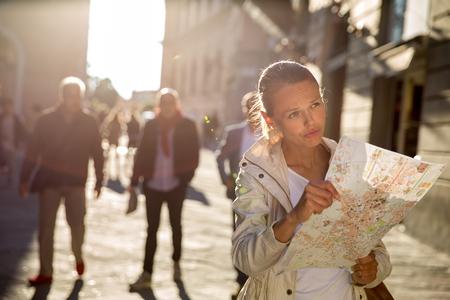 mochila de viaje: Turista femenino precioso con un mapa de descubrir una ciudad extranjera (DOF, imagen en color entonado) Foto de archivo