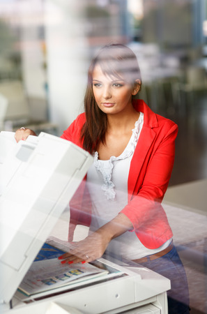 Pretty young female college studentsecretary using a copy machine (shallow DOF; color toned image) Stock Photo