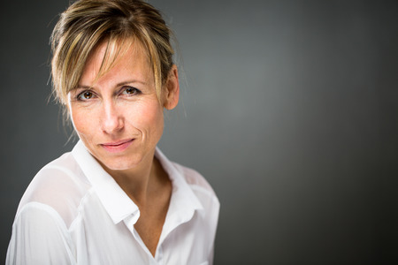 beautiful middle aged woman: Portrait of a smiling middle aged caucasian woman against dark background - radiating confidence and feminity (shallow DOF; color toned image)
