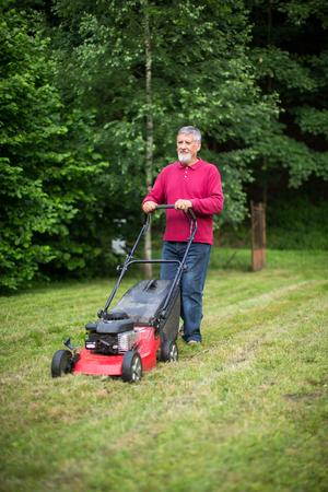 Älterer Mann, seinen Garten zu mähen