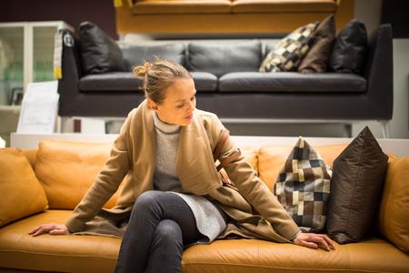 Mooie, jonge vrouw kiezen van de juiste meubilair voor haar appartement in een moderne winkel voor woninginrichting