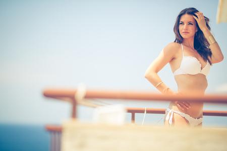 belles jambes: Beauté, spa et concept de station - beau, jeune femme par la mer sur un balcon d'une station  chambre d'hôtel Banque d'images