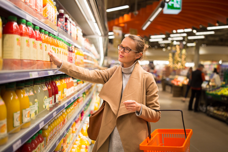 fashionable woman: Pretty, young woman shopping for her favorite fruit juicesmoothie at a grocery store