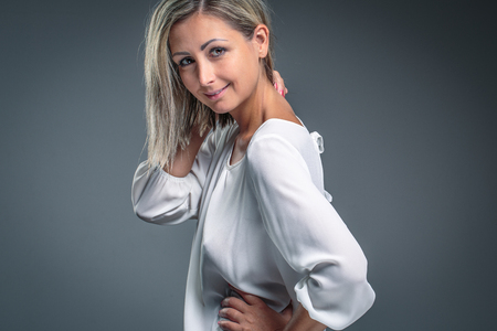Gorgeous young woman against grey background photo