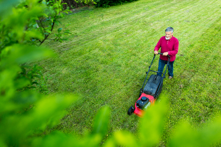 grass cutting: Senior man mowing his garden - shot from above - interesting angle view Stock Photo