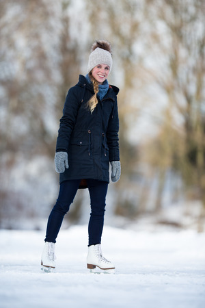 Young woman ice skating outdoors on a pond on a freezing winter day Stock Photo