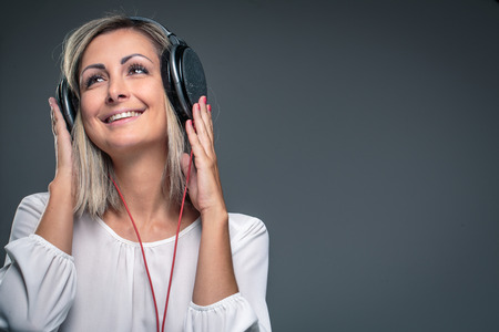 Pretty, young woman listening to her favorite music on hi-fi headphones, dancing, enjoying the tune, having a moment for herself photo