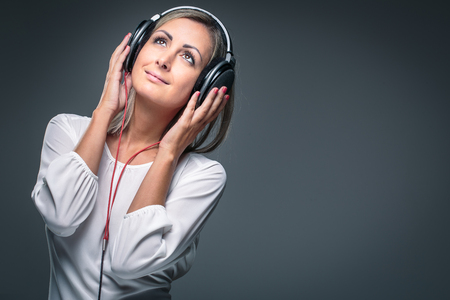 Pretty, young woman listening to her favorite music on hi-fi headphones, dancing, enjoying the tune, having a moment for herself Stock Photo