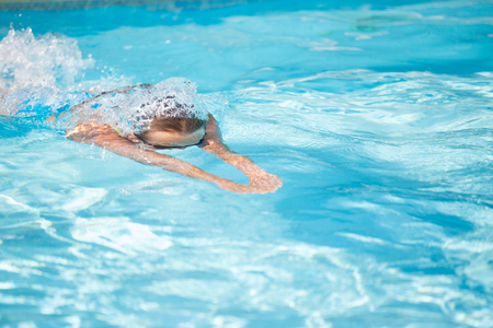 staying fit: Pretty female swimmer in a pool, getting her daily dose of exercise without stressing her joints