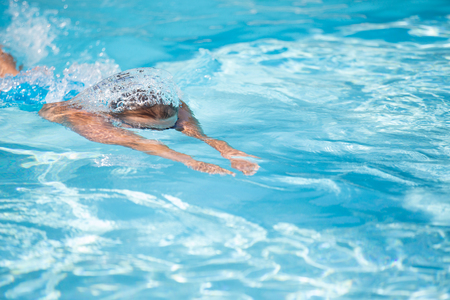 Pretty female swimmer in a pool, getting her daily dose of exercise without stressing her joints