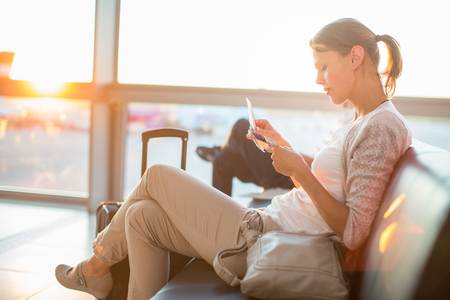 Young female passenger at the airport, waiting for her flight lit by warm evening light, about to board her flight, checking her boarding pass (shallow DOF; color toned image) Stock Photo