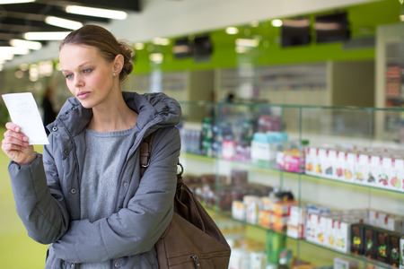 grippe: Young woman looking for the right pills in a modern pharmacy (shallow DOF; color toned image)