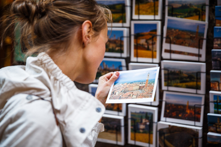 Young woman choosing the right postcard to send home from a vacation abroad (shallow DOF; color toned image)