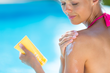 Attractive, young woman with healthy skin applying suncream by a pool (shallow DOF; color toned image) Stock Photo
