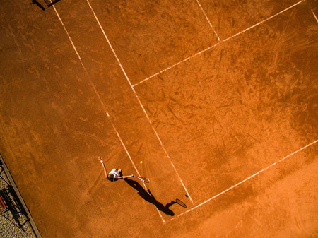 Female tennis player on the court. Wide angle view from above with plenty of copyspace Фото со стока